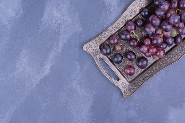 Une grappe de raisin dans un plateau métallique.