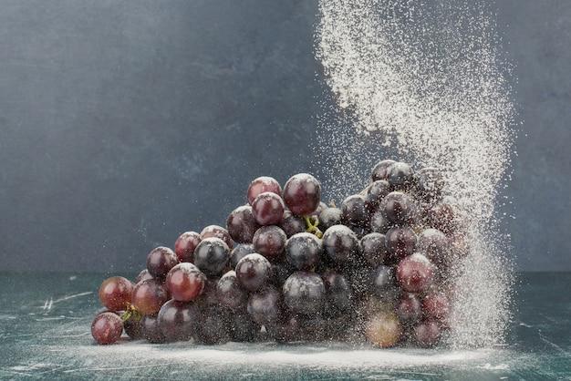 Grappe de raisin noir décoré de poudre sur table en marbre.