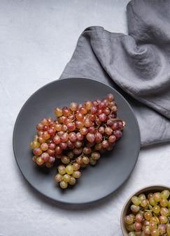 Une grappe de raisin rose vert juteux dans une assiette grise avec serviette sur une table lumineuse. vue de dessus