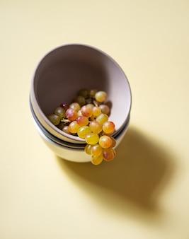 Une grappe de raisin rose vert juteux dans un bol gris sur fond jaune. vue de dessus et espace de copie