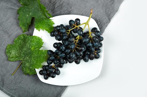 Une grappe de raisin rouge dans une assiette blanche.