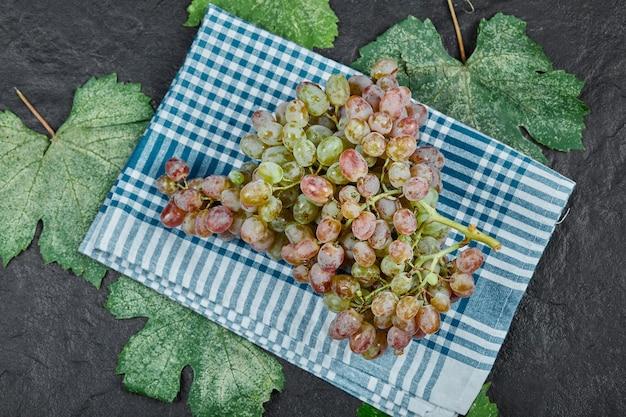 Une grappe de raisin rouge avec des feuilles et une nappe bleue sur fond sombre. photo de haute qualité