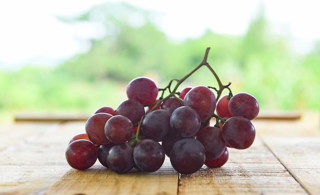 Grappe de raisin rouge sur la table en bois et la nature