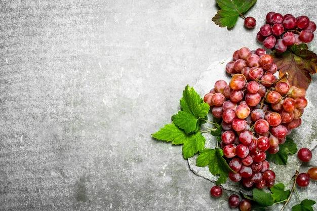 Grappe de raisin rouge sur table en pierre.