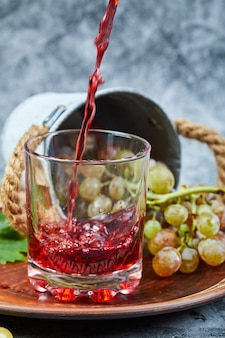 Grappe de raisin et un verre de jus sur marbre.