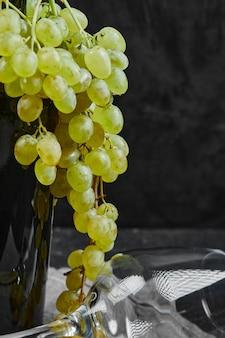 Une grappe de raisin vert sur la bouteille de vin.