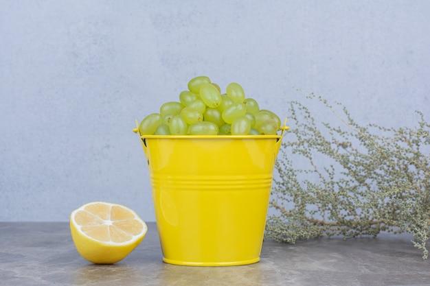 Grappe de raisin vert dans un seau avec demi-citron coupé.