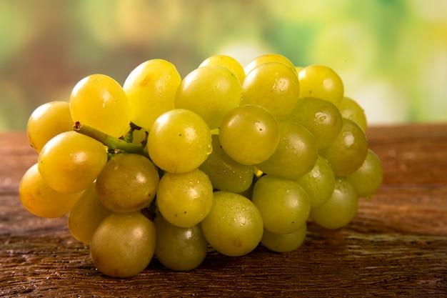 Grappe de raisin vert, fruits d'automne, symbole d'abondance sur fond de bois rustique.