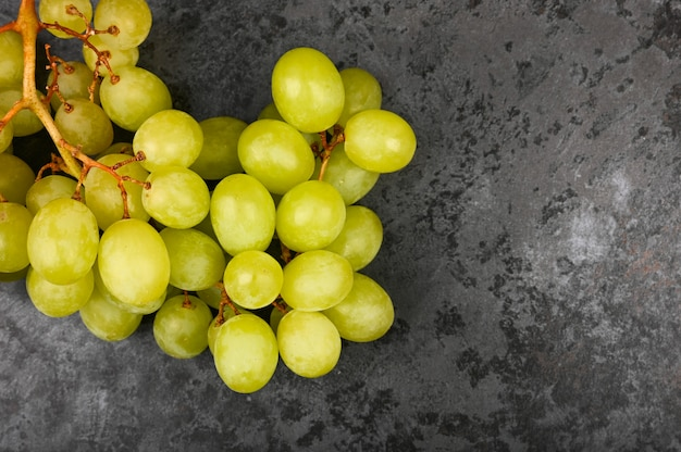 Une grappe de raisin vert repose sur du marbre