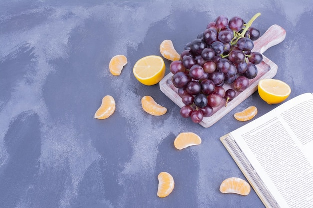 Une grappe de raisins de cuve sur une planche de bois.