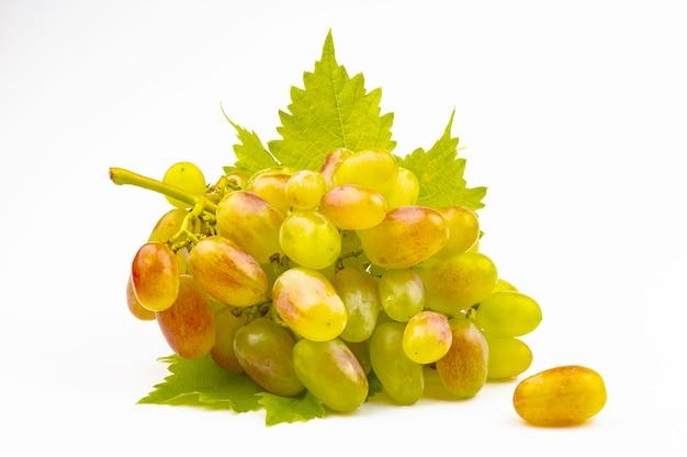 Une grappe de raisins frais jaune-rose avec un gros plan de feuille verte isolé sur fond blanc.