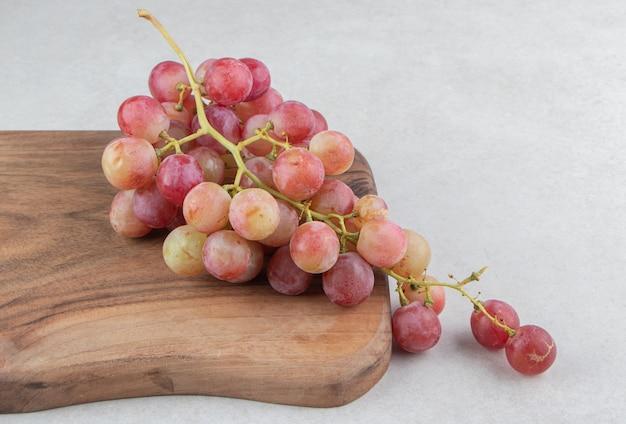 Grappe de raisins frais sur planche de bois.
