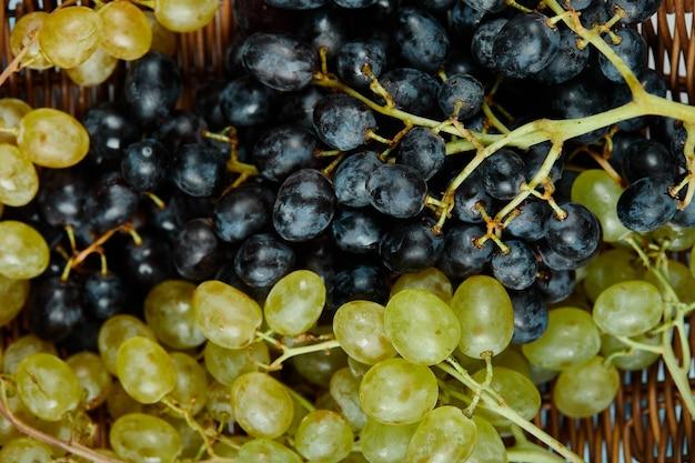 Une grappe de raisins mélangés dans le panier, gros plan. photo de haute qualité