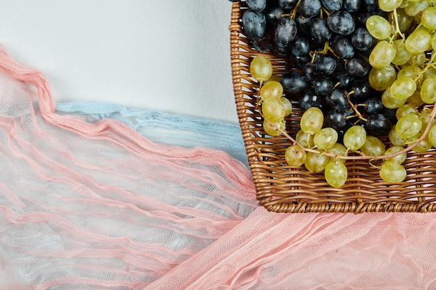 Une grappe de raisins mélangés dans un panier avec des nappes bleues et roses. photo de haute qualité