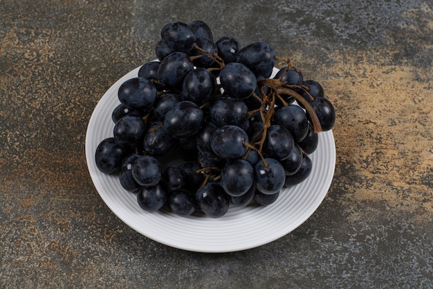 Grappe de raisins noirs sur plaque blanche.
