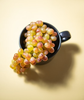 Une grappe de raisins roses verts juteux dans une tasse noire