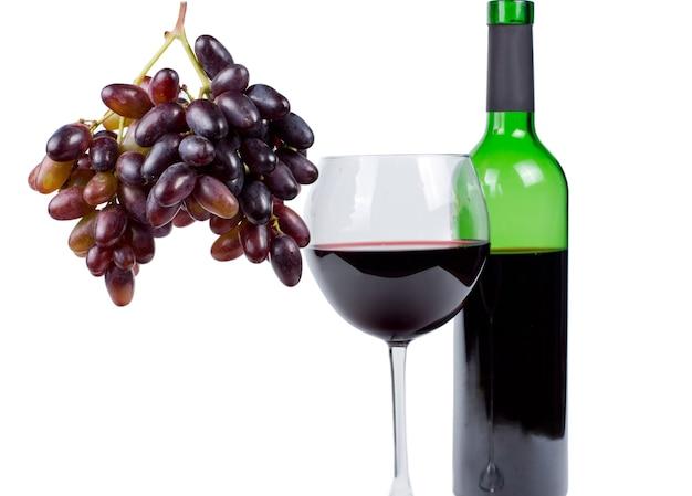 Grappe de raisins rouges mûrs frais accroché à côté d'un verre et d'une bouteille de vin rouge sans étiquette