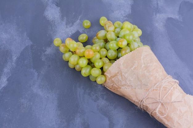 Une grappe de raisins verts sur table bleue.