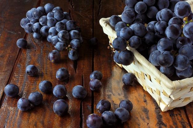 Grappes de raisin, à l'intérieur du panier de fibres de bambou sur la table en bois, vue