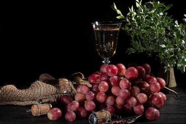 Grappes de raisins roses et pommes vertes sur une surface sombre. nature morte.