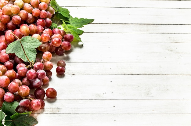 Grappes de raisins rouges avec des feuilles sur une table en bois blanche.