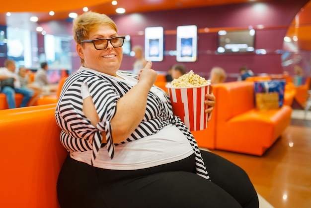 Grasse femme mangeant du pop-corn dans la salle de cinéma