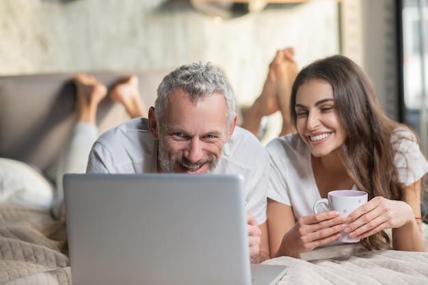 Une grasse matinée. un couple restant dans le lit avec café et ordinateur