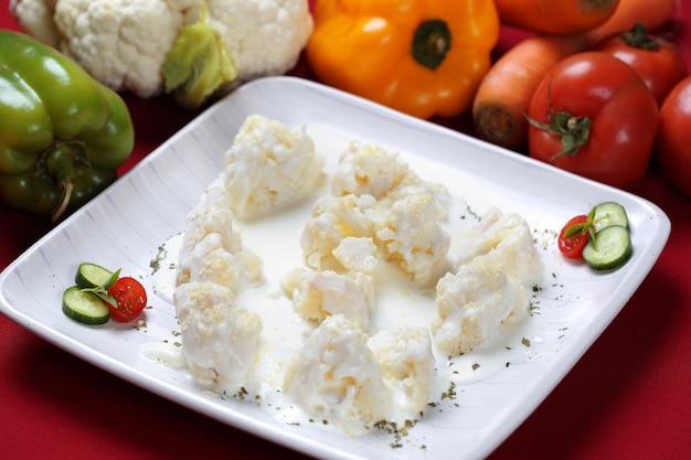 Gratin de chou-fleur aux légumes dans une assiette blanche.