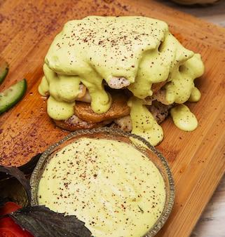 Gratin de poitrine de poulet et pommes de terre avec vinaigrette au fromage fondu au concombre sur planche de bois.