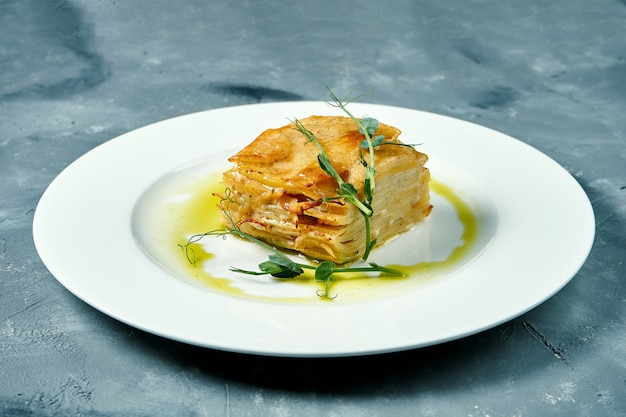 Gratin de pommes de terre au four avec crème et fromage dans une assiette blanche sur une surface en béton