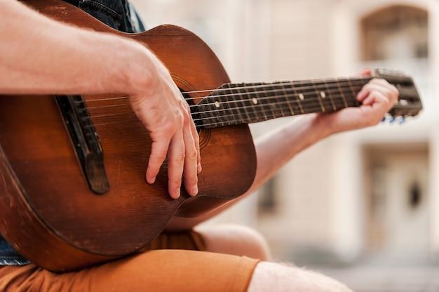 Grattage occasionnel. gros plan d'un jeune homme jouant de la guitare alors qu'il était assis à l'extérieur