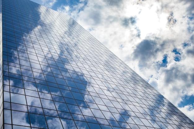 Gratte-ciel contre le ciel sur la vitre du bâtiment
