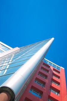 Gratte-ciel avec fenêtres en miroir et ciel bleu clair, vue de dessous