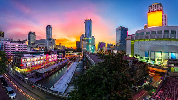 Gratte-ciel et jetée de pratunam à bangkok; transport de l'eau par bateau rapide