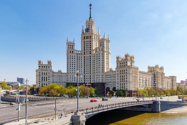 Gratte-ciel de staline sur le quai de kotelnicheskaya à moscou sur fond de pont malyi ustyinskiy en matinée ensoleillée