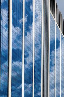 Gratte-ciel en verre contre le ciel bleu nuageux, fenêtres fortement réfléchissantes