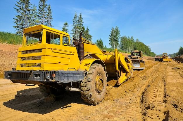 Un grattoir de tracteur jaune nivelle le sol construction d'une nouvelle route