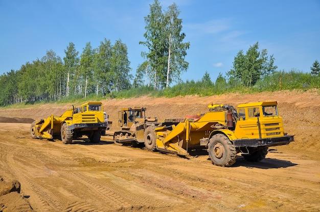 Le grattoir de tracteur jaune nivelle le sol d'une nouvelle route en été