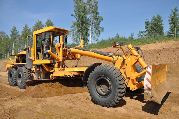 Le grattoir de tracteur nivelle le sol d'une nouvelle route