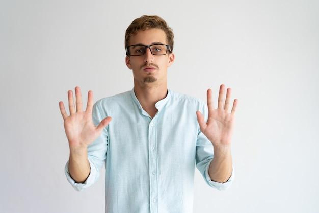 Grave beau mec dans des verres en levant les mains en signe d'arrêt