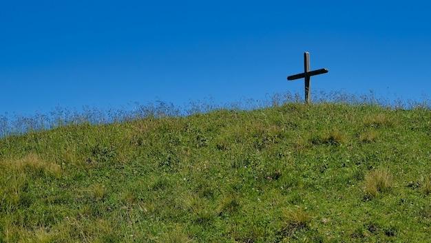 Grave hill avec une croix avec de l'herbe contre un ciel bleu en autriche