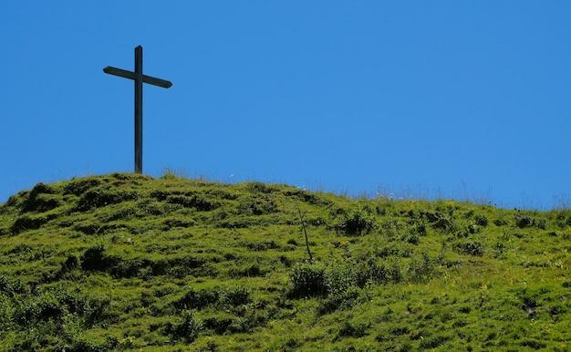 Grave hill avec une croix avec de l'herbe contre un ciel bleu