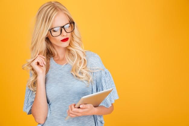 Grave jeune femme blonde à l'aide de la tablette tactile.