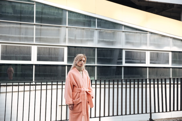Grave jeune femme blonde marchant à l'extérieur.
