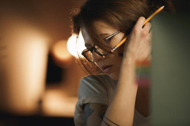Grave jeune femme designer assis à l'intérieur la nuit tenant un crayon