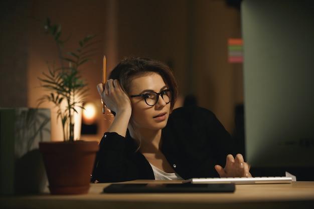 Grave jeune femme designer utilisant un ordinateur