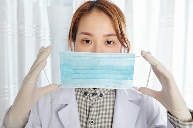 Grave jeune femme médecin généraliste dans des gants de protection mettant un masque médical