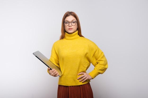 Grave jeune femme tenant un ordinateur portable