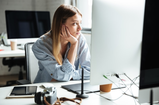 Grave jeune femme travaille au bureau à l'aide d'un ordinateur
