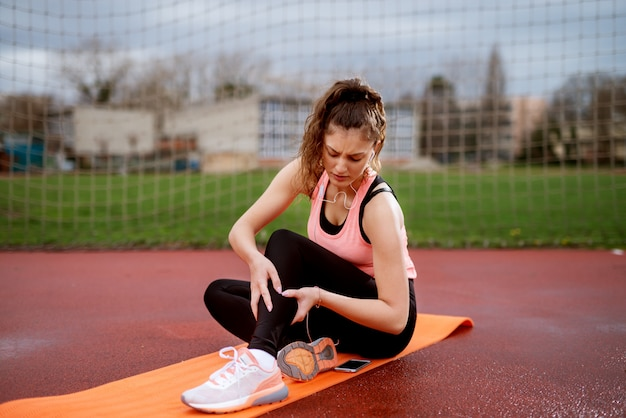 Grave jeune fille de remise en forme tenant la tige blessée alors qu'il était assis sur le tapis orange à l'extérieur près du terrain de football.
